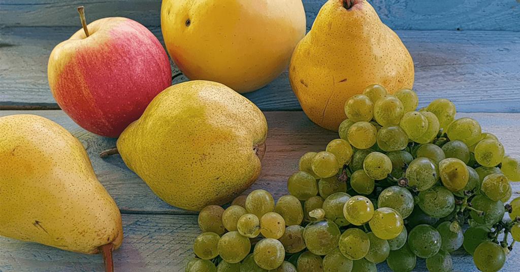 Ябълки, круши и зелено грозде на маса.